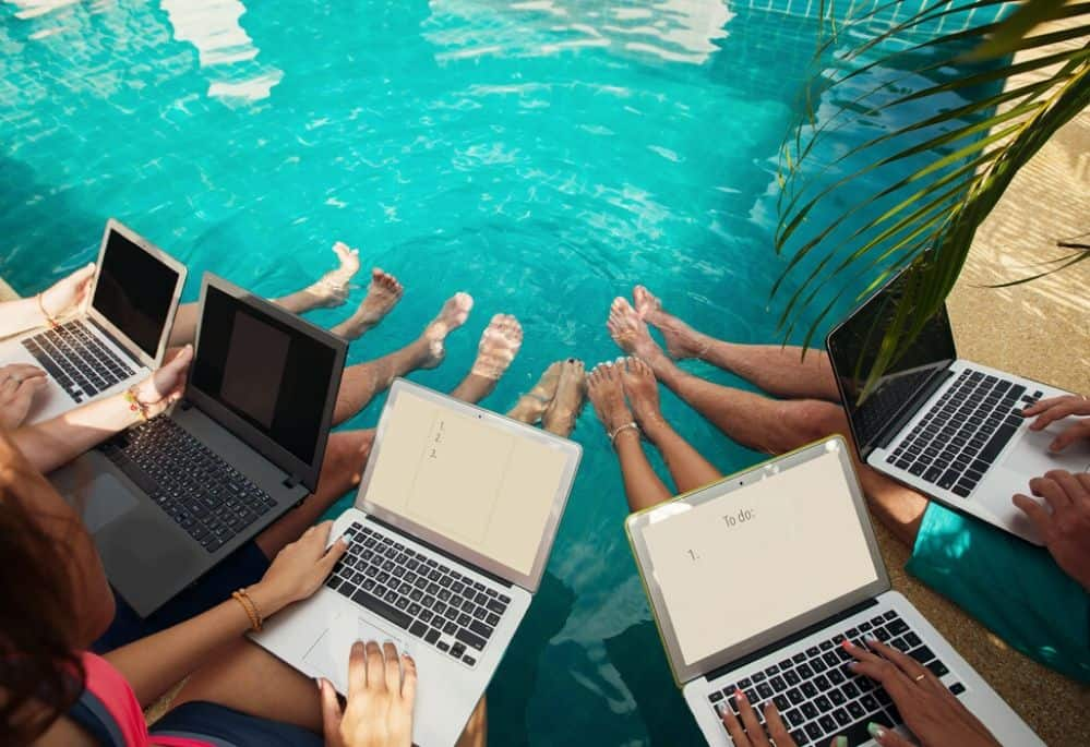 Peop;e on laptop working by pool. working online when on family vacation