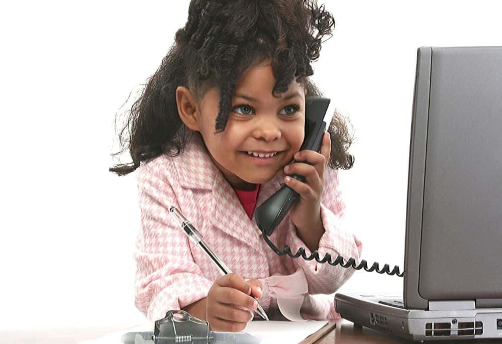 Child on phone and looking at laptop making business deals
