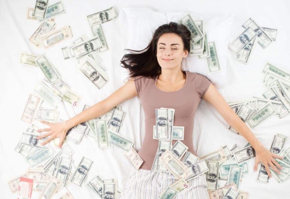 Woman lying on a bed of cash. Simple ways to earn a passive income