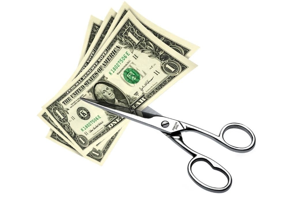 Cutting dollars in half with scissors as a symbol of spending cutbacks redcuing expenses and bills