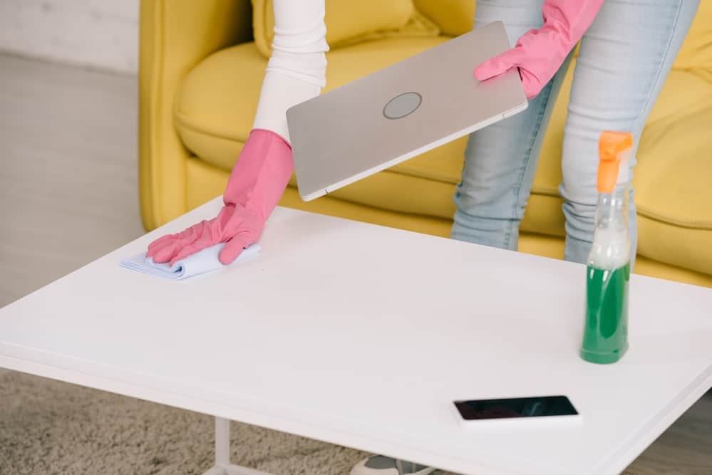 Woman cleaning home work station with laptop and smartphone during natural health disaster.