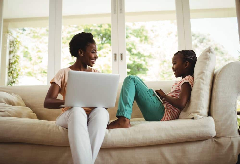 Mom and daughter on sofa while mom gets paid to type on laptop