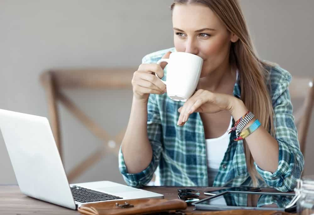 Woman drinking coffee working from home on laptop reading about FlexJobs